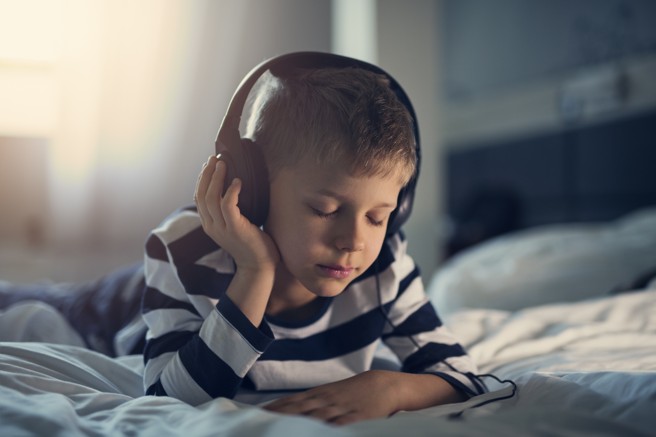Boy listening to podcasts in bed